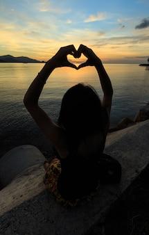 Heart finger symbol at dusk