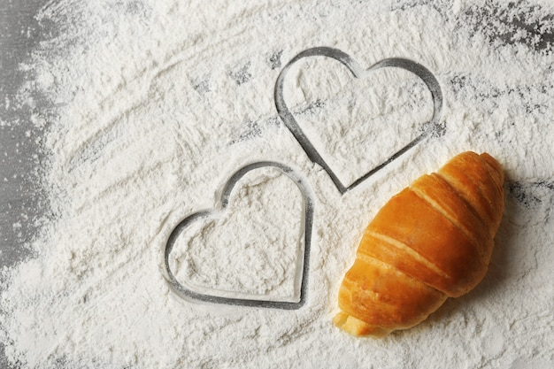 Heart of flour and fresh croissants on wooden table