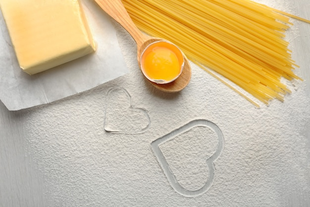 Heart of flour and pasta on gray surface
