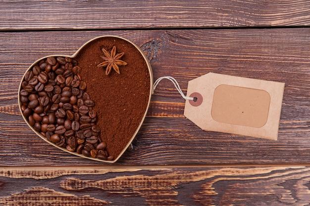 Форма сердца из кофейных зерен и растворимого кофе. пустой тег для копирования пространства. коричневая деревянная поверхность.