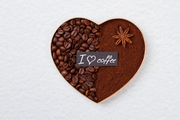 Форма сердца из кофейных зерен и порошка. изолированные на белой поверхности