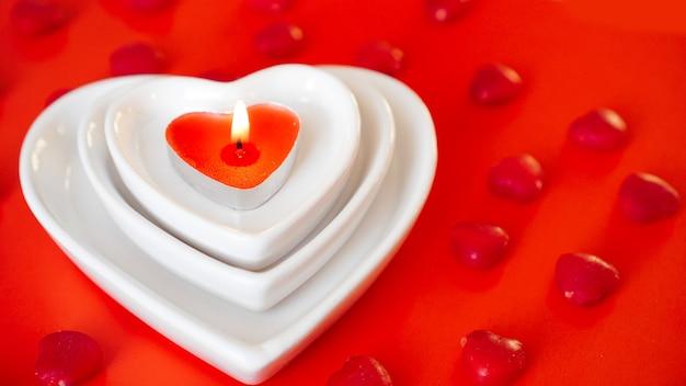 ハート形の白いプレートと小さなキャンディーと赤い背景の上のキャンドル-バレンタインデーのコンセプト