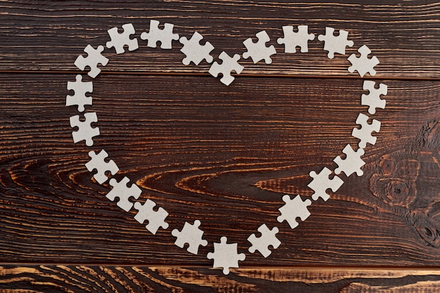골판지 퍼즐로 만든 하트 프레임. 어두운 나무 배경에 빈 직소 퍼즐에서 심장의 모양. 게임에 대한 사랑.