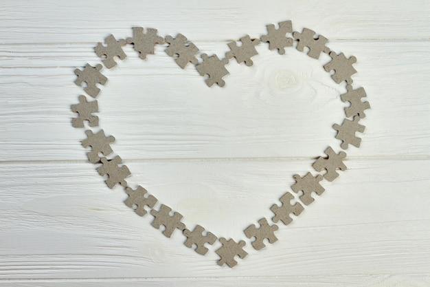 직소 퍼즐로 만든 하트 프레임. 밝은 나무 배경에 회색 골 판지 퍼즐에서 만든 심장의 모양.