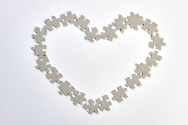 Heart frame made from puzzles. shape of heart from jigsaw puzzles over white background. happy valentines day.