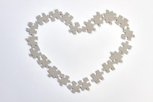 퍼즐에서 만든 하트 프레임입니다. 흰색 배경 위에 직소 퍼즐에서 심장의 모양. 행복한 발렌타인 데이.