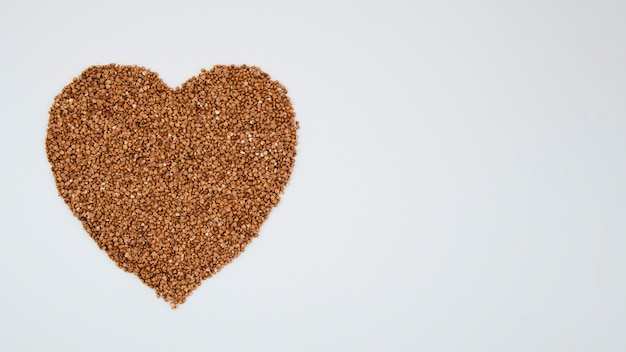 Heart from buckwheat on blue background with copy-space