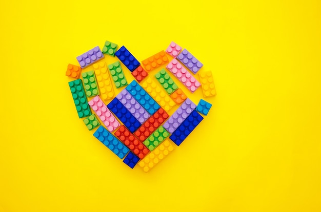 A heart from a children's multi-colored constructor on a yellow background. empty space for the text.holiday date.valentine's day.