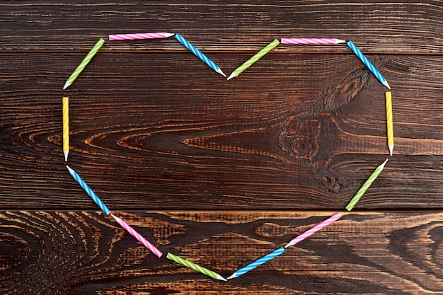 Сердце из красочных свечей дня рождения. рамка-сердце из свечей и копией пространства.