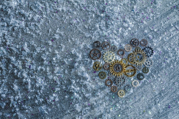 Heart from gears and cogs on silver background