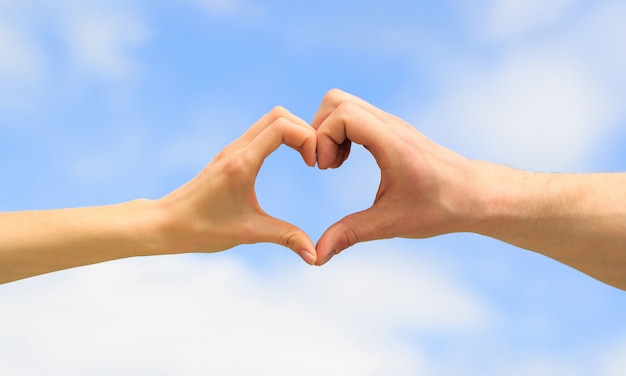 Heart from hands on a sky background. love, friendship concept.