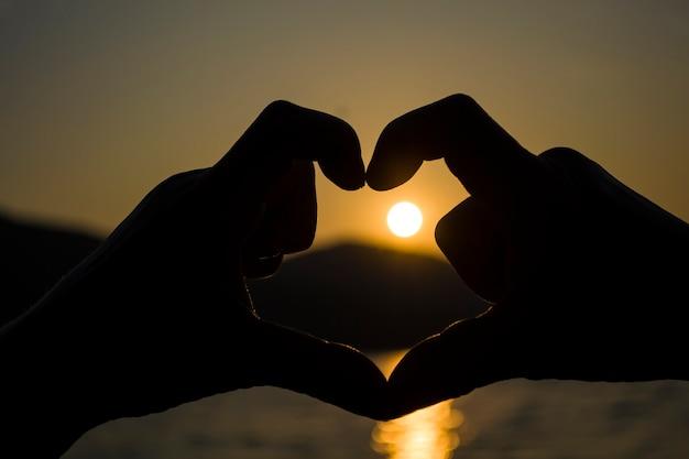 Сердце из рук, вечерний закат за горой на большом озере, романтический вид на закат на берегу ...