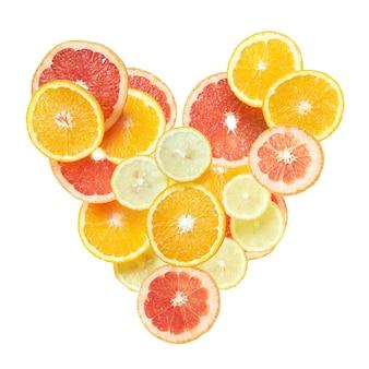 白い表面に分離されたオレンジ、レモン、グレープフルーツのスライスからの心