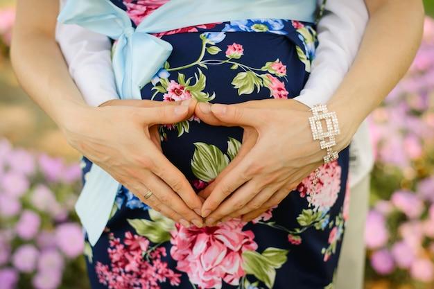 Сердце из рук мужа и жены на беременном животе