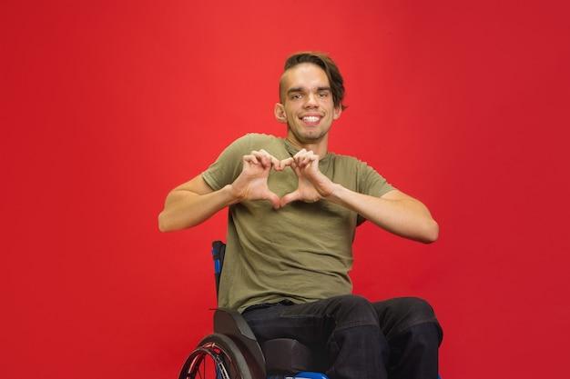 ハートジェスチャー。赤いスタジオの壁に白人の若い障害者の肖像画。コピースペース。