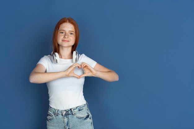심장 제스처입니다. 파란색 벽에 백인 어린 소녀의 초상화입니다. 귀여운 주근깨가 있는 아름다운 여성 redhair 모델입니다. 인간의 감정, 표정의 개념입니다.