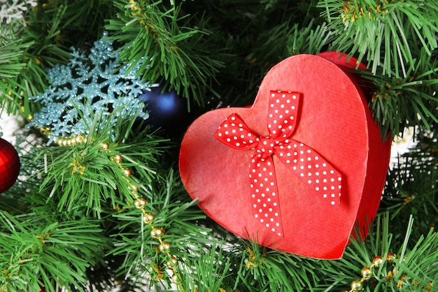 Сердце - подарочная коробка на фоне елки, крупным планом