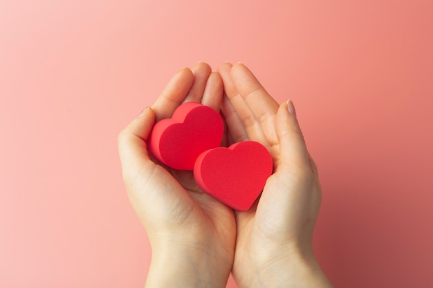 Heart in the hands of a female on a colored background. background for valentine's day (february 14) and love.
