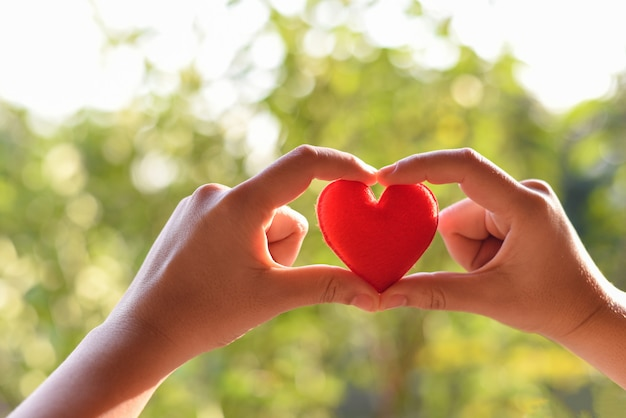慈善の概念-バレンタインの日のための手で赤いハートを保持している女性や愛の温かさを与える助けを与える女性 Premium写真