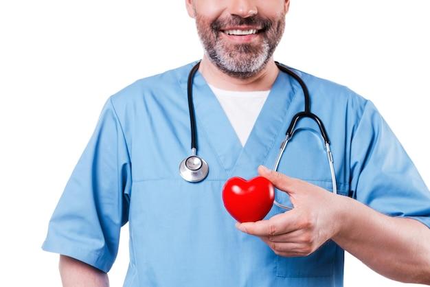 Сердце в руке. крупный план зрелого кардиологического хирурга, держащего игрушку в форме сердца и улыбающегося, стоя изолированным на белом