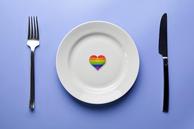 Сердце в цветах флага лгбт в пластине. романтические гей-знакомства в кафе или ресторане. в ожидании особого лгбт-гостя на свадебный банкет.
