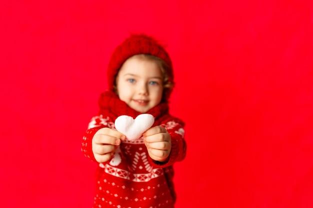 빨간색 배경에 겨울 옷에 어린 소녀의 손에 마음. 새해 또는 발렌타인 데이 개념, 텍스트를위한 장소