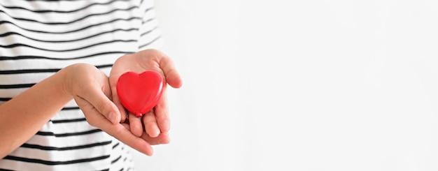 Сердце в руках женщины на белом фоне с днем матери или международным днем семьи