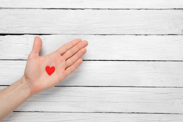 Сердце в руке мужчины на деревянном