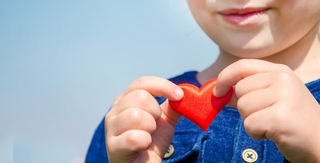 The heart is in the hands of the child. selective focus.