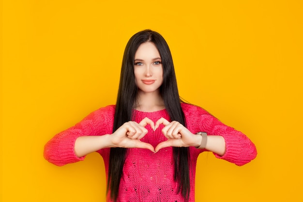 The heart is made of hands, made by a girl on a bright yellow wall, in a pink sweater. the concept is made with love, give love, the emotion of trust and sympathy