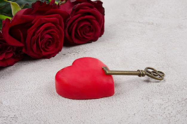 Heart, a key and a bouquet of roses on a gray marble background