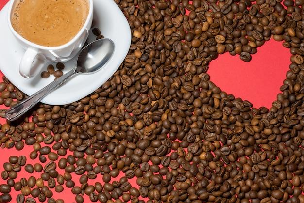 淹れたてのコーヒーのカップと赤い背景の上のコーヒー豆からレイアウトされたハート