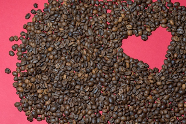 赤い背景の上のコーヒー豆からレイアウトされたハート
