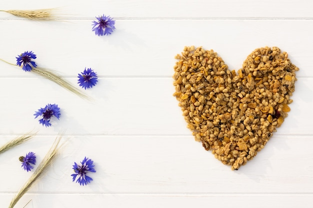 Сердце из мюсли, колосков и васильков на белом деревянном фоне. плоская планировка. скопируйте пространство.