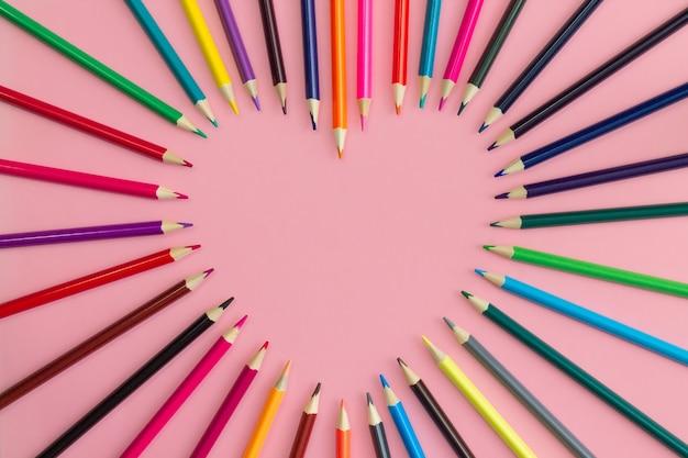 분홍색 배경, 평면 누워, 복사 공간에 날카롭게 멀티 컬러 연필로 뻗어 심장.