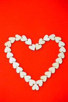 Сердце выложено деревянными сердечками на ярко-красном фоне. место для надписи, романтического рисунка на день всех влюбленных.