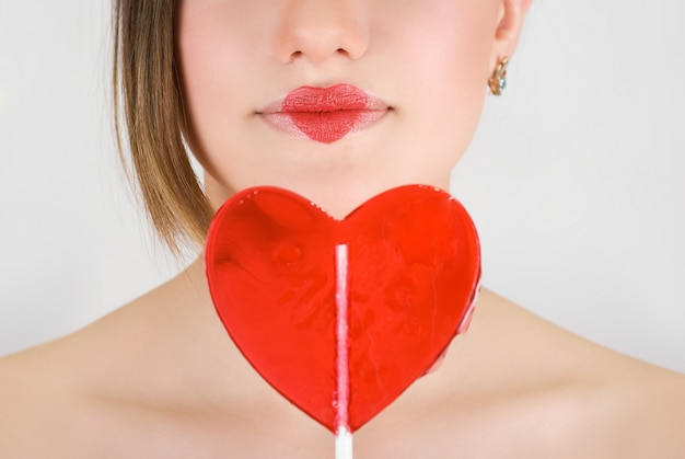 Heart on lips of pretty woman closeup with heart lollipop