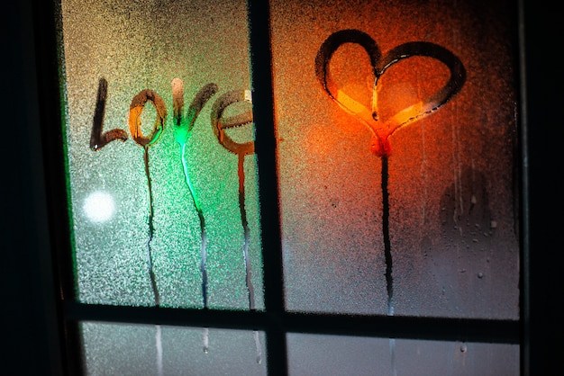 Heart and love inscription on the fogged glass against