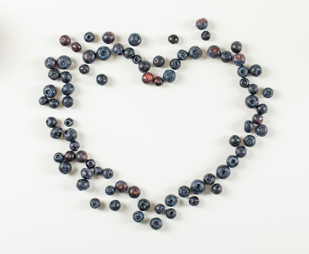 Heart made of blueberries on a white surface. flat lay.
