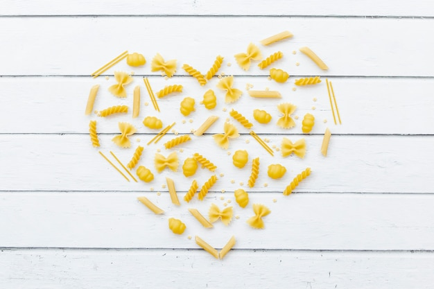 Heart made by different types of pasta on wooden table