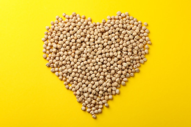 Heart made of chickpea on yellow