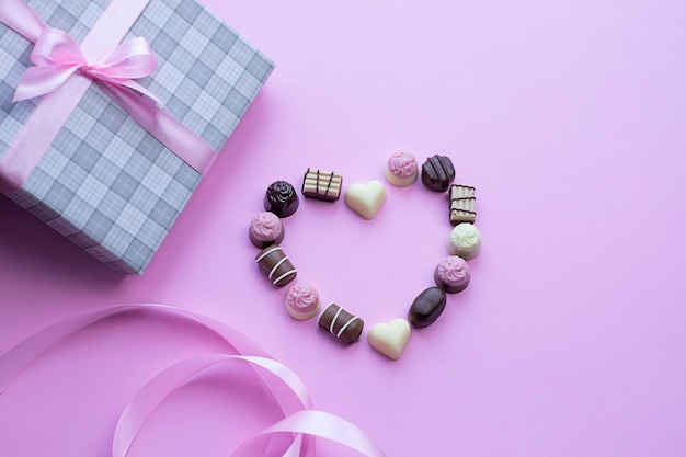 Heart made of chocolate pralines on pink background image with copy space