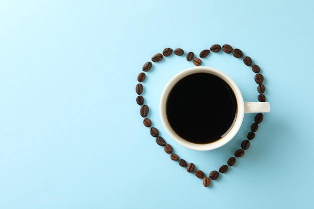 Heart made of coffee beans and cup of coffee
