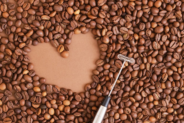 Heart made of coffee beans and metal handheld milk steamer on brown background. handheld frother