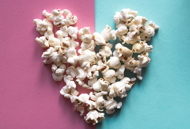 Heart made of delicious popcorn on pink pastel and blue pastel color background
