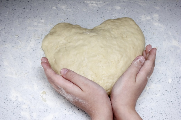 A heart made of dough is held by children's hands.