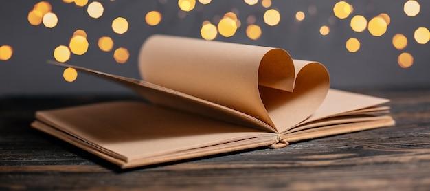 Сердце из книжных листов в концепции огней, любви и валентинки на деревянном столе