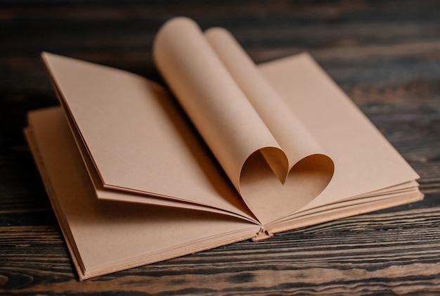 Сердце из книжных листов, концепция любви и валентинки на деревянном столе