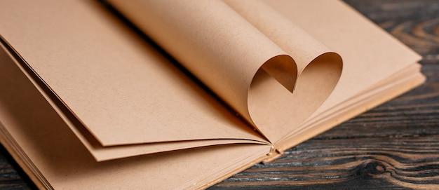 나무 테이블에 책 시트, 사랑과 발렌타인 개념에서 만든 심장