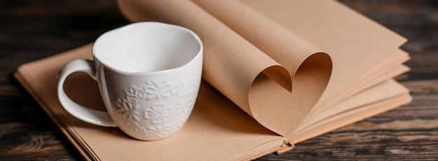 Сердце из книжных листов с концепцией чашки, любви и валентинки на деревянном столе